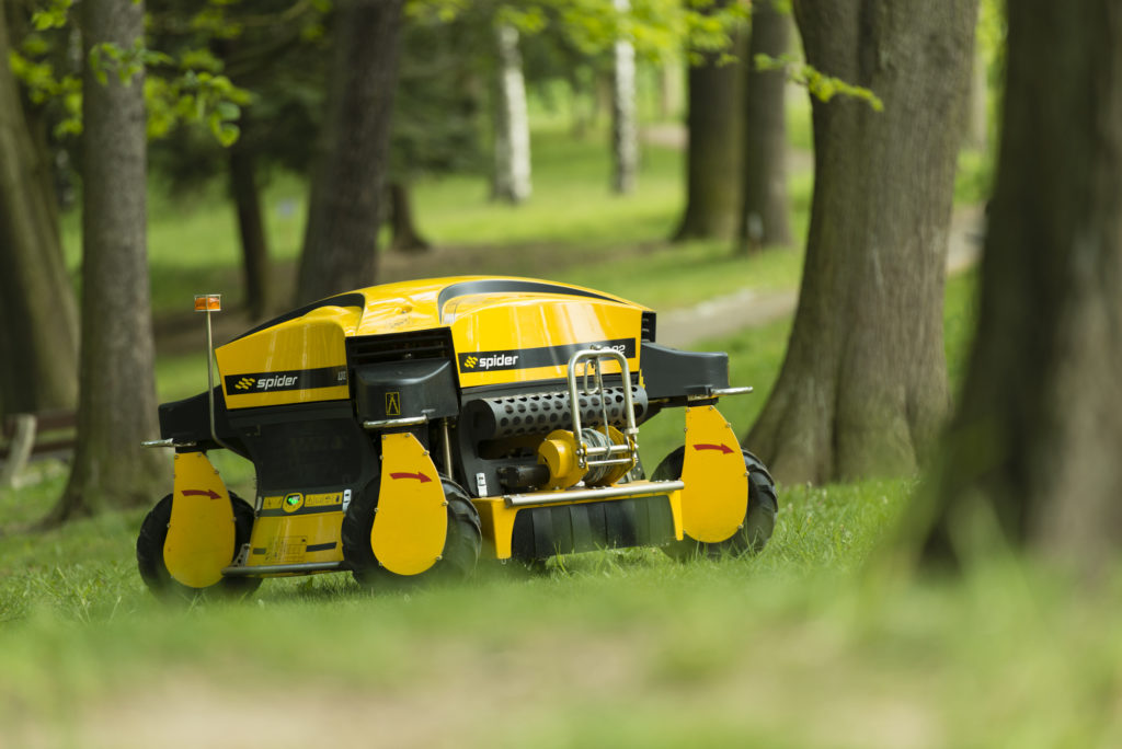 Spider ILD02 Remote Control Slope Mower Stopped on the Grass Surrounded by Trees