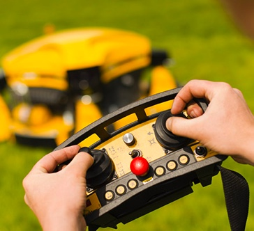 Closeup of Person Operating Spider Slope Mower Using a Remote Control