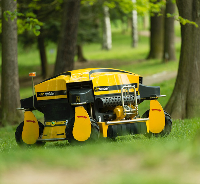 Spider ILD02 Slope Mower Stopped on the Grass Surrounded by Trees