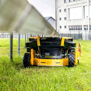 Spider Slope Mower Mowing Grass Underneath a Solar Panel