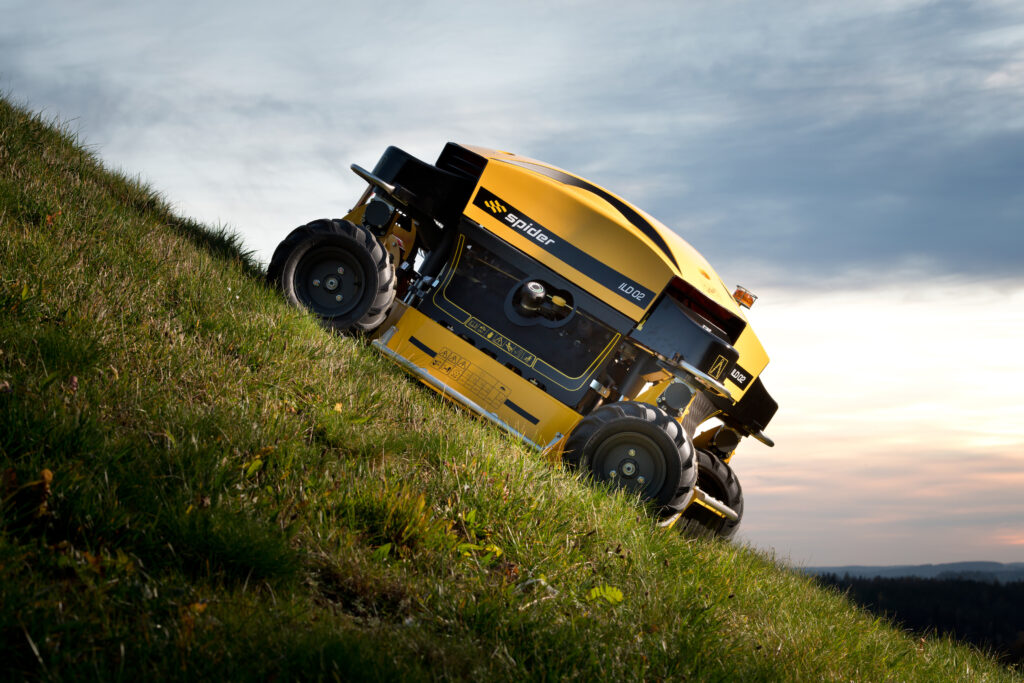 Spider steep slope mower mowing hill during sunset