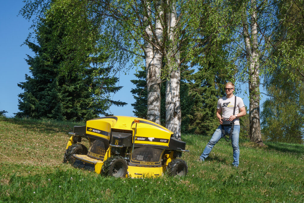 man on a hill professionally cutting grass with a remote control commercial mower