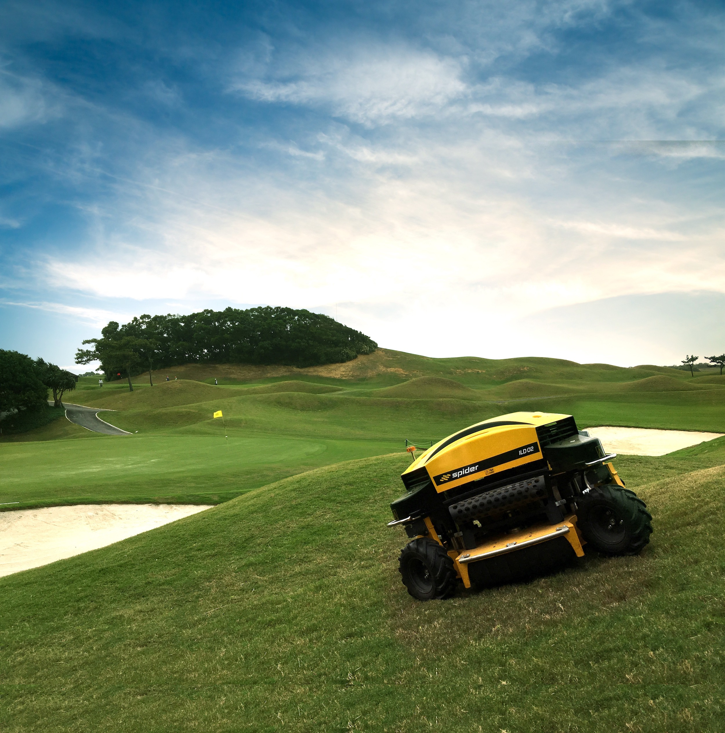 The Spider ILD02 Remote Control Slope Mower Mowing Grass on a Golf Course on a Sunny Day