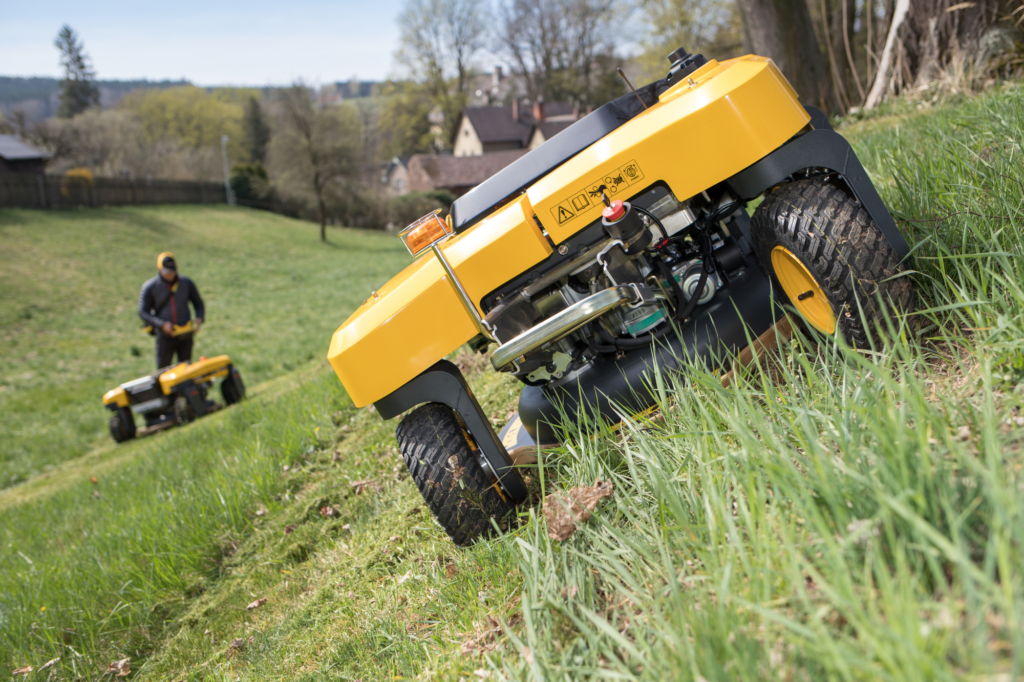 SPIDER slope mower working on a steep hill with the operator standing at the bottom